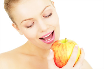 Attractive girl eats an apple isolated on white background