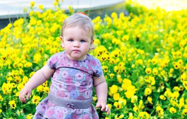 baby girl near pansy