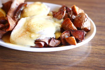 Eggs benedict, bacon, and potatoes
