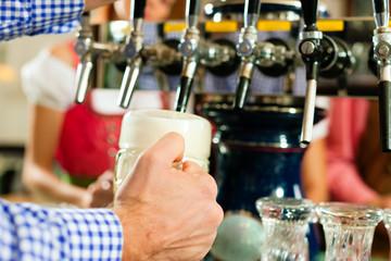 Mann zapft Bier in Bayerischer Wirtschaft