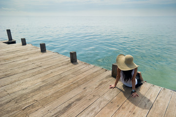 woman with big hat relaxing at the dock