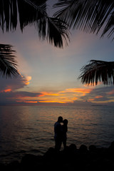 romantic silhouette couple kissing in the sunset