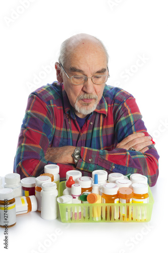 elderly man looking at his meds