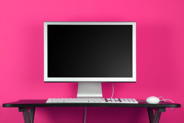 Desktop computer and pink wall - home office concept