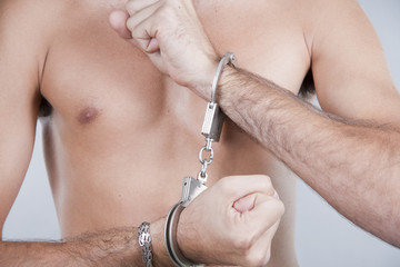 close-up man's hands chained in handcuffs