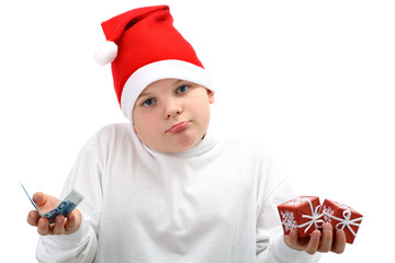 Boy in Santa's hat holding Christmas presents and money isolated