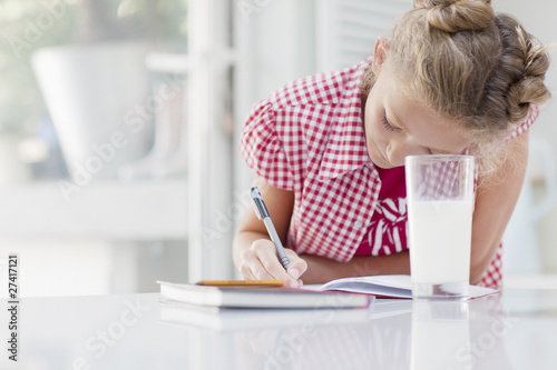girl doing homework with glass of milk