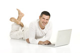 man dressed in white lying on the floor with laptop