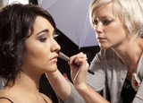 Make-up artist working on model at photoshoot. poster