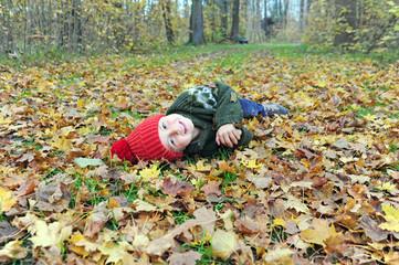 Junge tobt im Laub