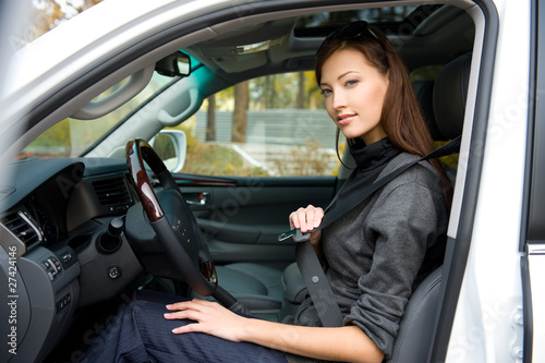 woman fastens a seat belt in the car
