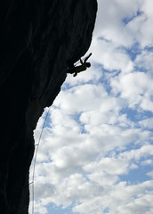 Silhouette of rock climber climbing cliff
