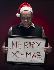 Horror Christmas Elf holding a sign written with blood.