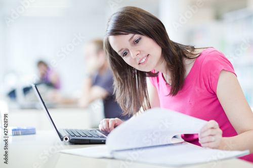 in the library - pretty female student with laptop and books wor