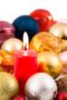 Rote Kerze im Weihnachtsbaumkugelmeer
