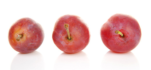 Three healthy plums over white background