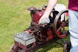 Mechanic Oiling Vintage Restored Red Stationary Engine with Spin poster