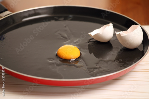 Cracked egg in cooking pan with eggshells
