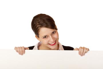 glückliche Frau hält lachend leeres Schild für Werbung / Reklame