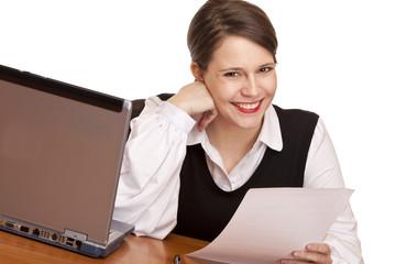 Junge lachende Frau sitzt im Büro und arbeitet an Compu