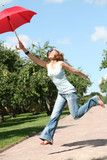 smiling girl jumping with red umbrella