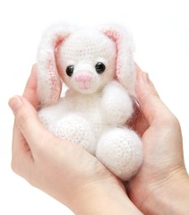 hands holdin a toy hare with caress