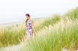 Model girl walking in sand dunes beach