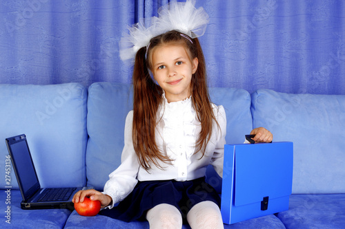 Schoolgirl with laptop, case and red apple in sofa