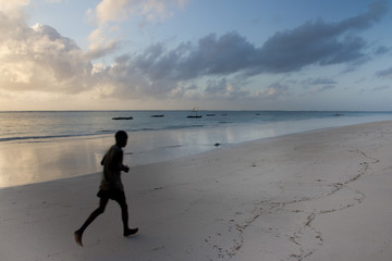 Young man jogging on white sand beach