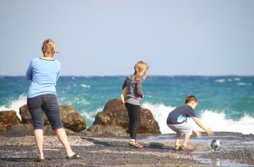 Mutter mit spielenden Kindern am Meer