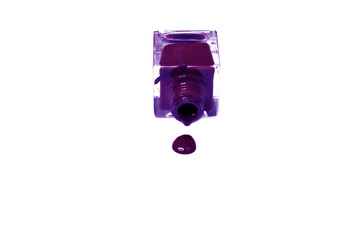 violet nail polish bottle with splatters isolated on white backg