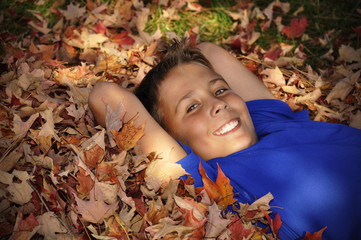 preteen boy laying in autumn leaves