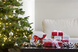 presents by christmas tree in modern living room