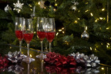 four wine glasses and ribbons by christmas tree