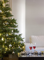 two drinks and bows by christmas tree in modern living room