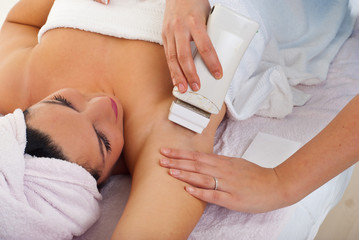 Beautician waxing woman's armpit