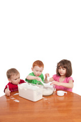 Kids measuring and mixing flour in kitchen bowl
