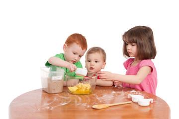 Kids measuring ingredients for baking in kitchen