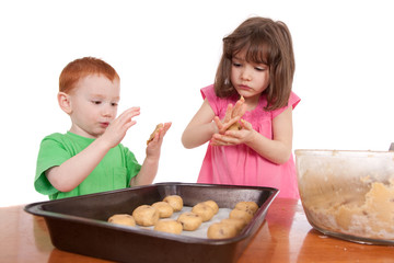 Kids rolling out chocolate chip cookies for baking