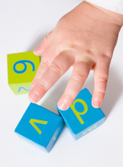 Early Learning - Child's Hand Playing with Alphabet Blocks