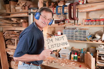 Senior man in workshop not listening