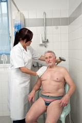 Senior wird von Pflegepersonal gebadet