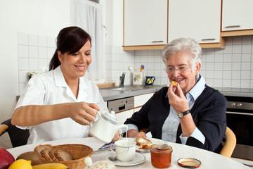 Pflegerin hilft Seniorin beim Frühstück
