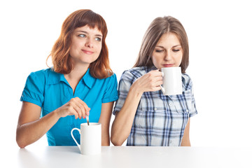 Two teen-girls are drinking tea