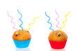 two colorful muffins decorated with festive candles isolated ove