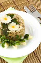 Aspic from chicken meat decorated with eggs and parsley