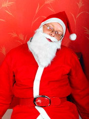 tired santa claus sleeps in a chair
