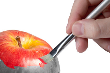 Male hand painting a fresh red wet apple