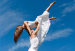 young couple dancing on sky background, freedom and relax symbol