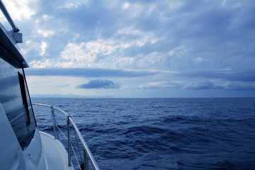 Boat sailing in cloudy stormy day blue ocean